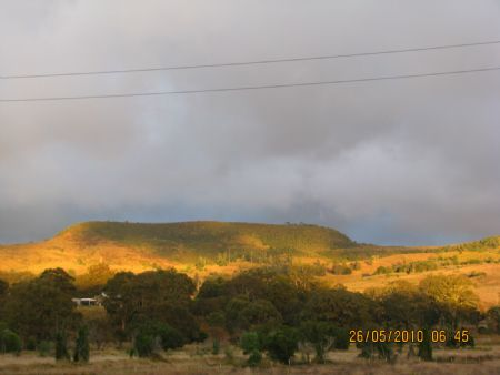 sunrise hits the hill across the valley